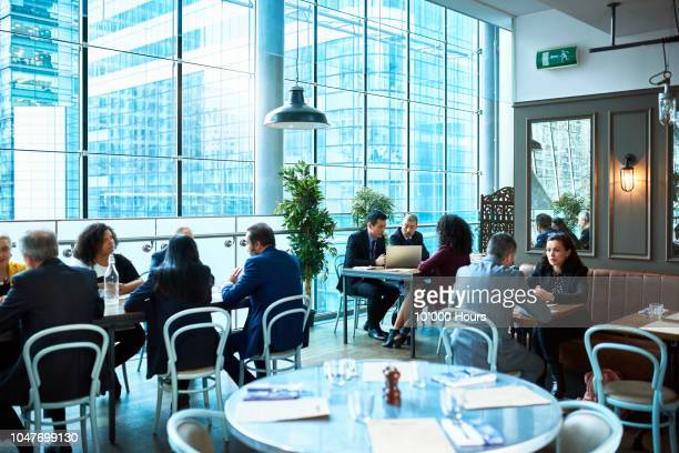 business people sitting at tables in restaurant over lunch - wide shot stock pictures, royalty-free photos & images