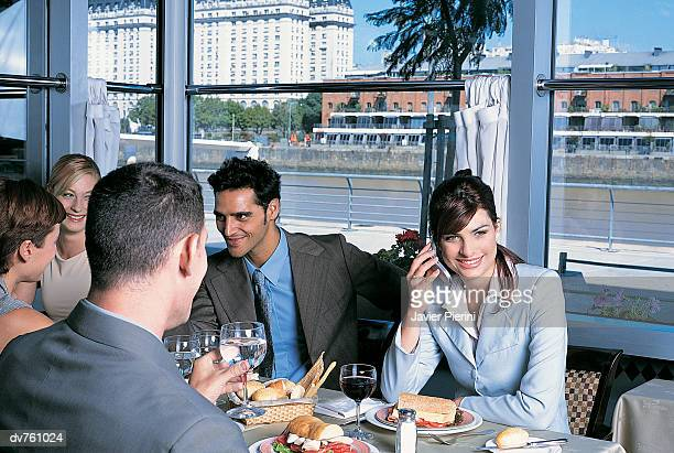 Business People Sitting in a Restaurant and a Businesswoman Using Her Mobile Phone