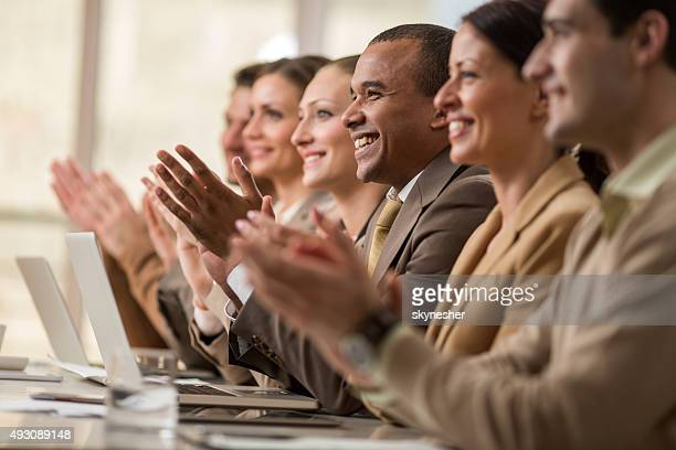 Business people sitting in a row and applauding.