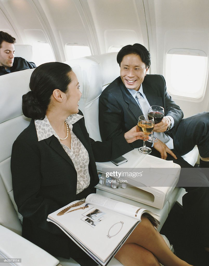 Business People Sitting in an Aircraft Enjoying a Glass of Wine : Stock Photo