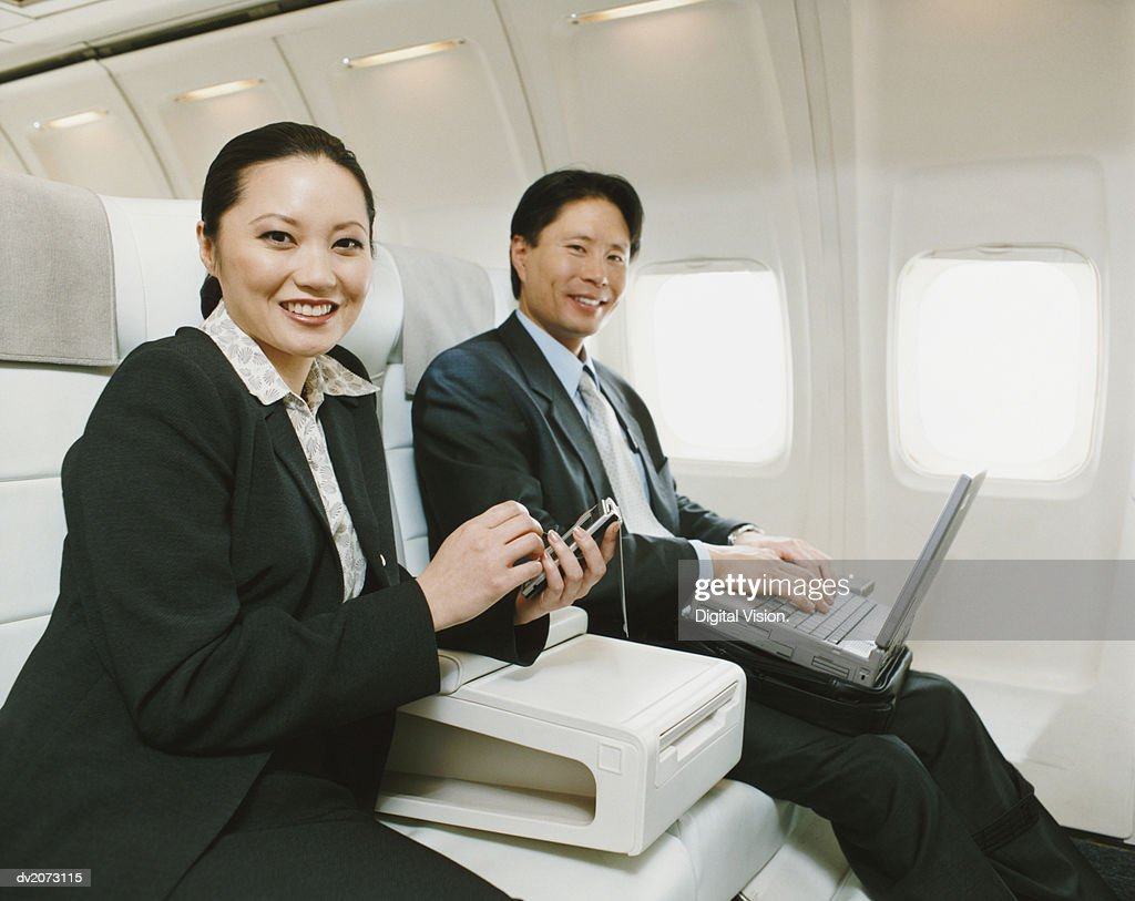 Business People Sitting in an Aircraft With Palm Pilot and Laptop : Stock Photo