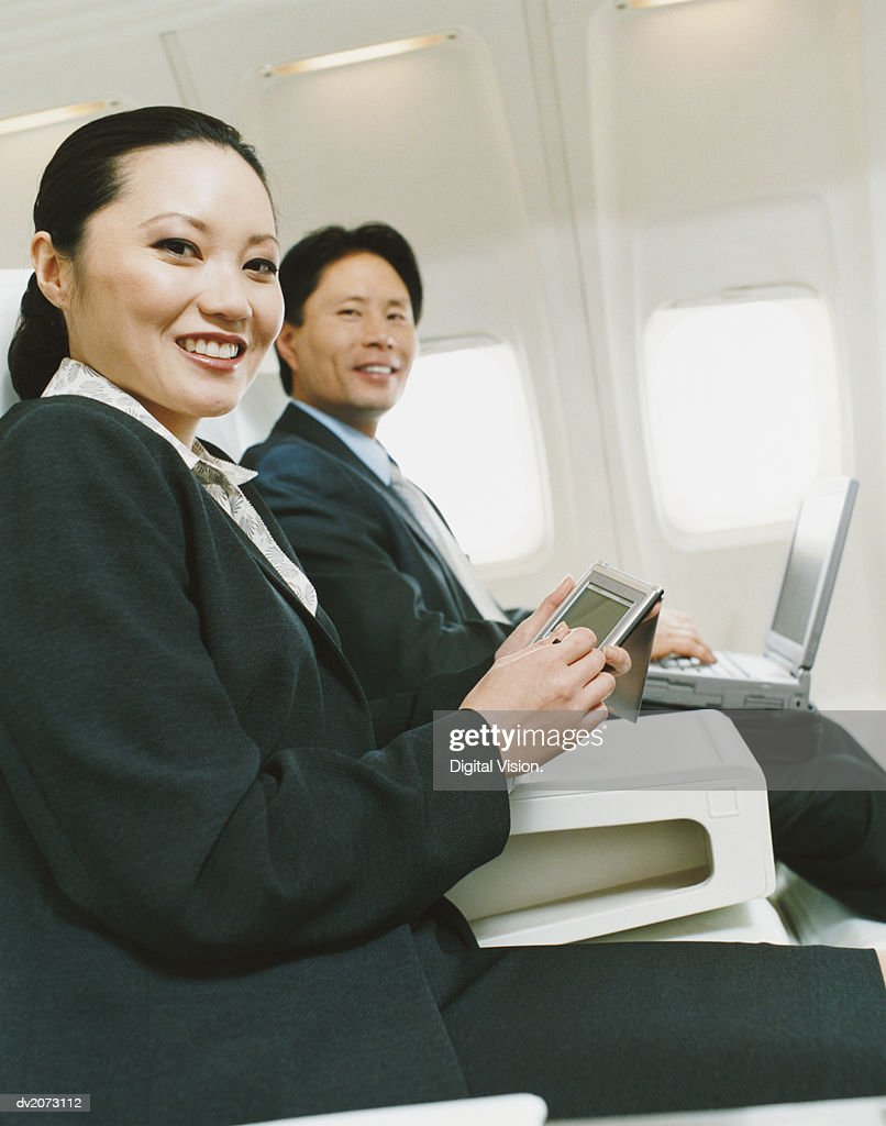 Business People Sitting in an Aircraft With Palm Pilot and Laptops : Stock Photo