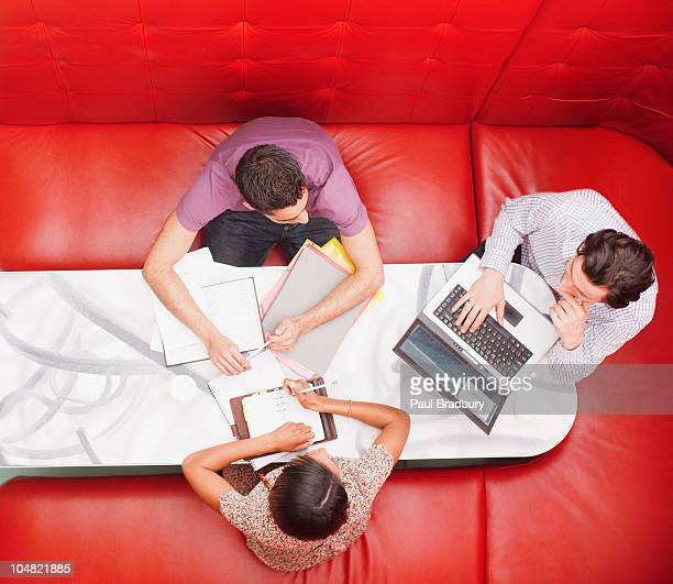 business people sitting in booth having a meeting - red background stock photos and pictures