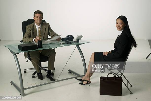 Business people sitting in chairs, posing in studio, portrait
