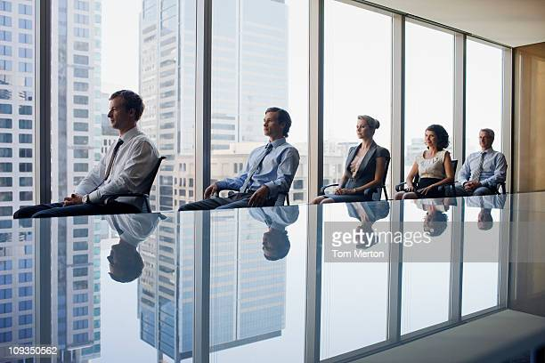 Business people sitting in row together in conference room