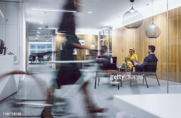 geschäftsleute sitzen im korridor, arbeiten - bewegungsunschärfe stock-fotos und bilder