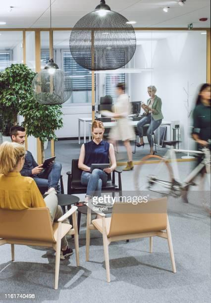 geschäftsleute sitzen im korridor, arbeiten - coworking stock-fotos und bilder