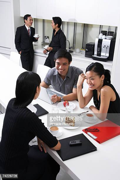 Business people sitting in work kitchen