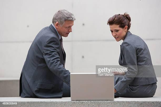 Geschäftsleute sitzen auf überfüllten Tisch mit laptop