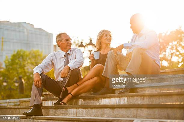 Business people sitting on staircase at sunset and talking.
