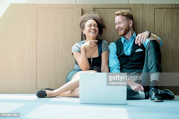 Business people sitting on the floor and smiling