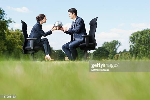 Business people sitting outdoors holding globe