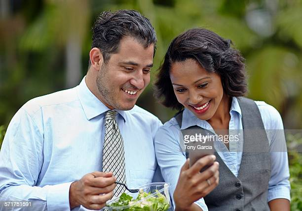 Business people sitting side by side enjoying a salad on lunch break, looking at smartphone, smiling
