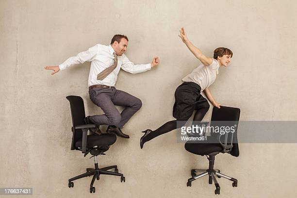 Business people skating on office chair