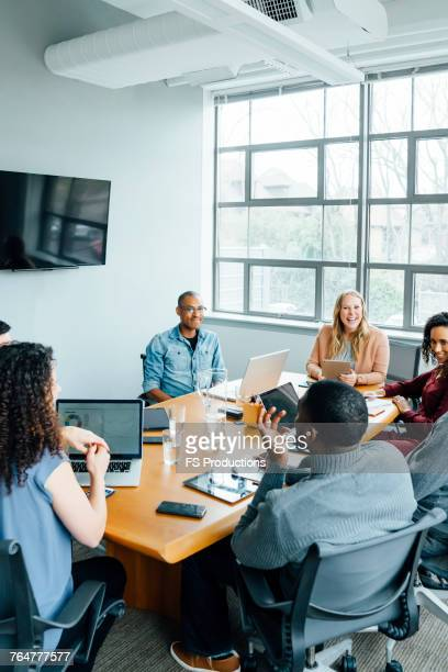 business people smiling in meeting - dedication stock pictures, royalty-free photos & images
