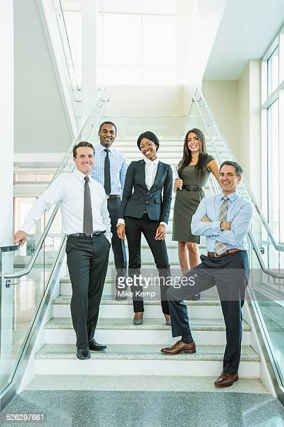 business people smiling on office staircase - formal businesswear stock pictures, royalty-free photos & images