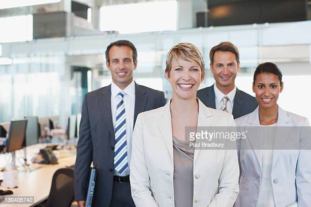 business people smiling together in office - four people stock pictures, royalty-free photos & images