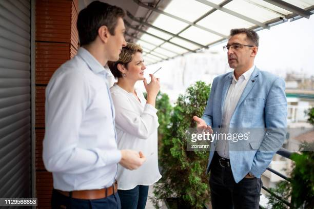 business people smoking on a break - smoking issues stock pictures, royalty-free photos & images