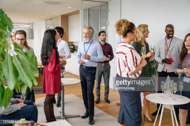 geschäftsleute, die sich bei einer büroveranstaltung mit champagner verabcieren - unterhaltungsveranstaltung stock-fotos und bilder
