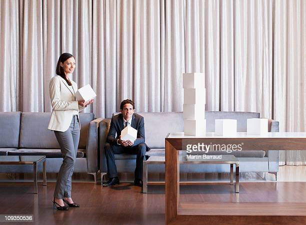 Business people stacking cubes in  hotel lobby