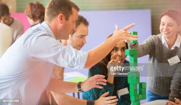 Business people stacking green blocks