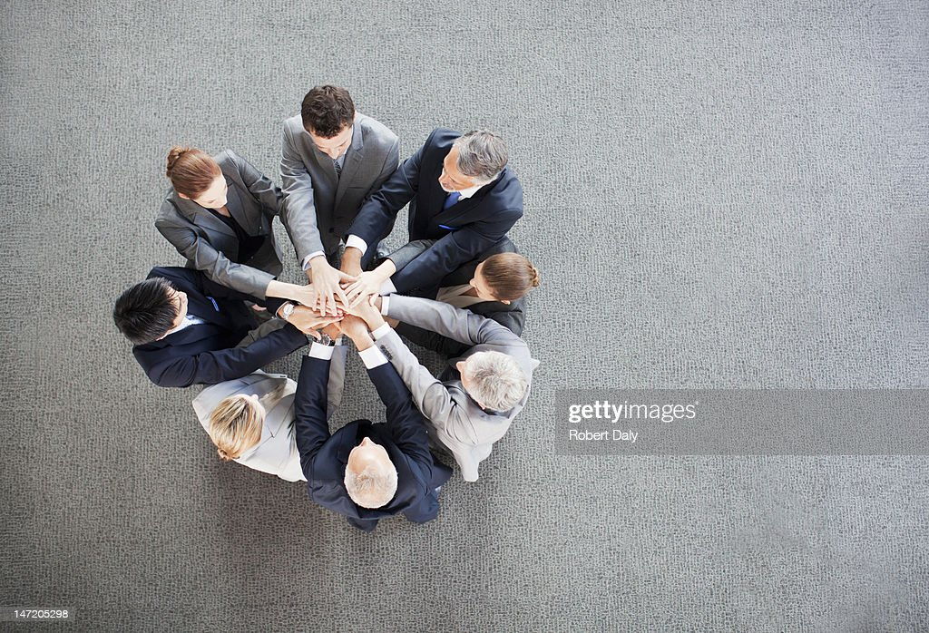 Business people stacking hands in circle : Stock Photo