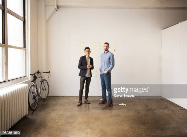 business people standing against white wall in creative office - smart casual stock pictures, royalty-free photos & images