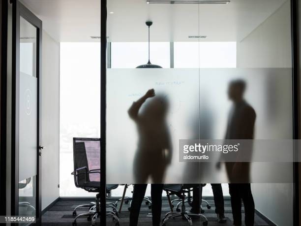 business people standing and writing on transparent board - shadow stock pictures, royalty-free photos & images