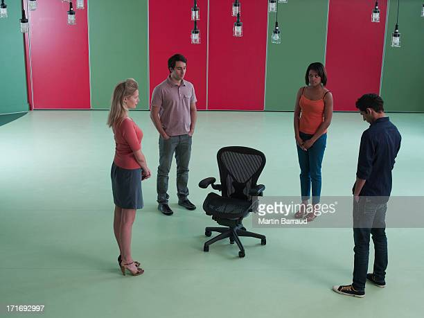 Business people standing around empty chair