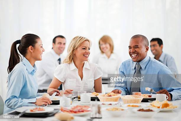 Business people standing around table at lunch