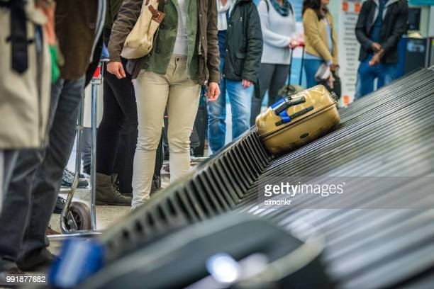 business people standing at baggage claim - baggage claim stock photos and pictures