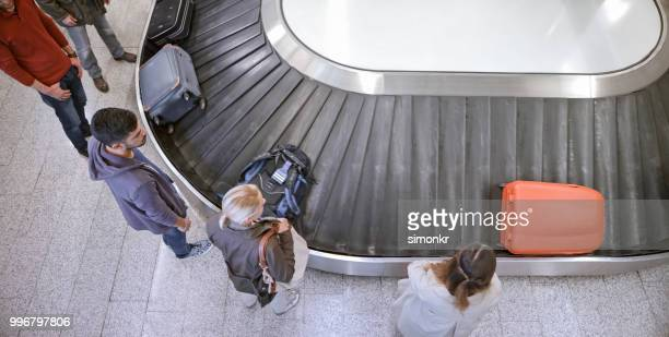 business people standing at baggage claim - baggage claim stock pictures, royalty-free photos & images