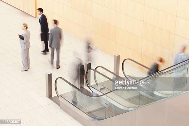 Geschäftsleute stehen am unteren Ende der Rolltreppe