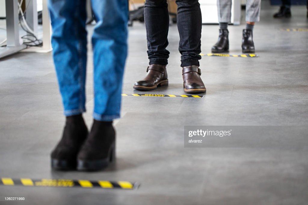 Bedrijfsmensen die zich achter sociale distantiërende bewegwijzering op bureauvloer bevinden : Stockfoto