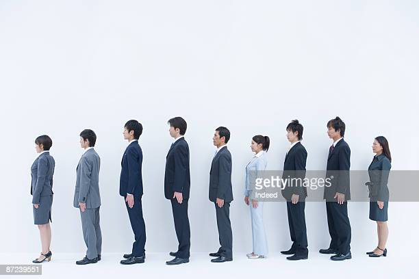 Business people standing in a row, side view