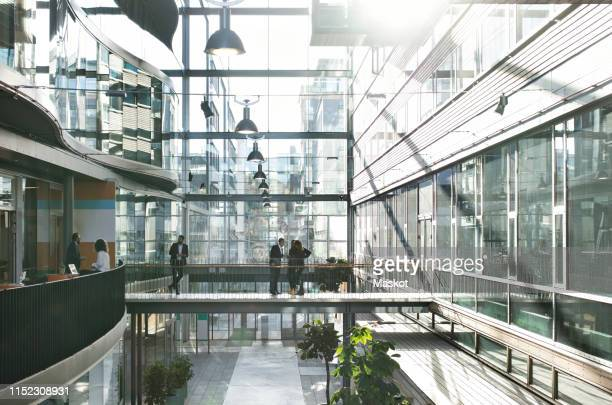 business people standing in atrium at modern office - building atrium stock pictures, royalty-free photos & images