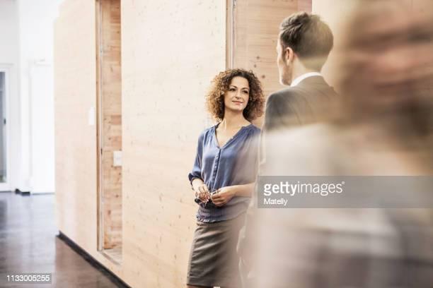 business people standing in busy hallway - bewegungsunschärfe stock-fotos und bilder