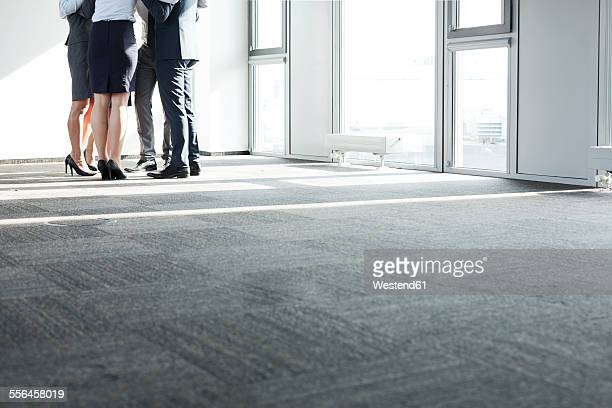 Business people standing in circle, arms around