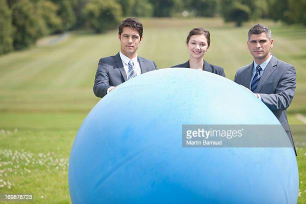 business people standing in field with large ball - man with big balls stock photos and pictures