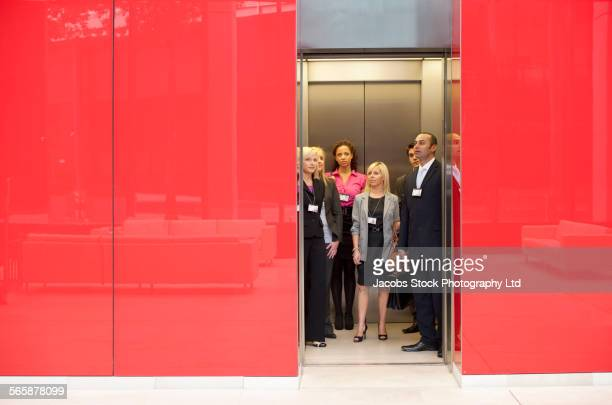 Business people standing in office elevator