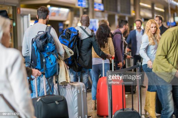 business people standing in queue at airport - long hair stock pictures, royalty-free photos & images
