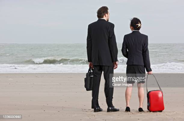 business people standing on empty beach - middelburg netherlands stock pictures, royalty-free photos & images