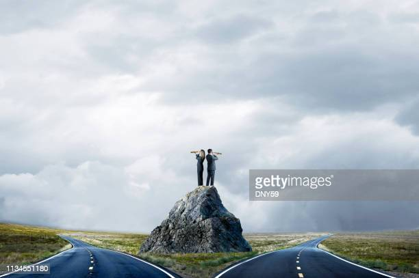 business people standing on large rock looking at fork in the road - forked road stock pictures, royalty-free photos & images