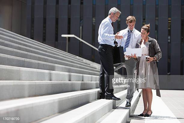 Business people standing on steps outdoors
