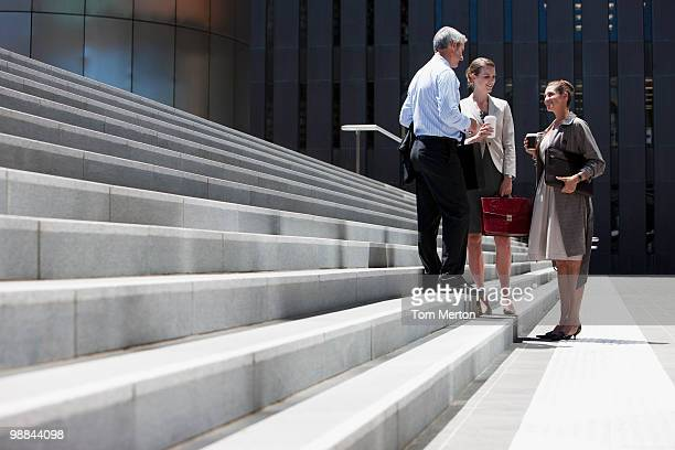 business people standing on steps outdoors - formal businesswear stock pictures, royalty-free photos & images
