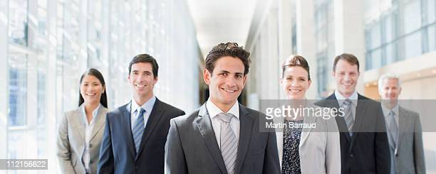 business people standing together in office - full suit stock pictures, royalty-free photos & images