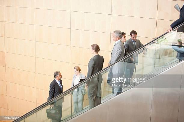 Geschäftsleute gehen auf Rolltreppe