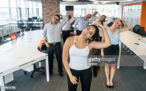 Business people stretching while taking a break from work at the office