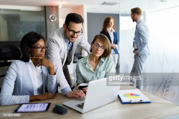 Business people studying statistic report using laptop