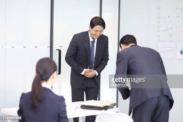 business people taking bow in meeting - お辞儀 ストックフォトと画像